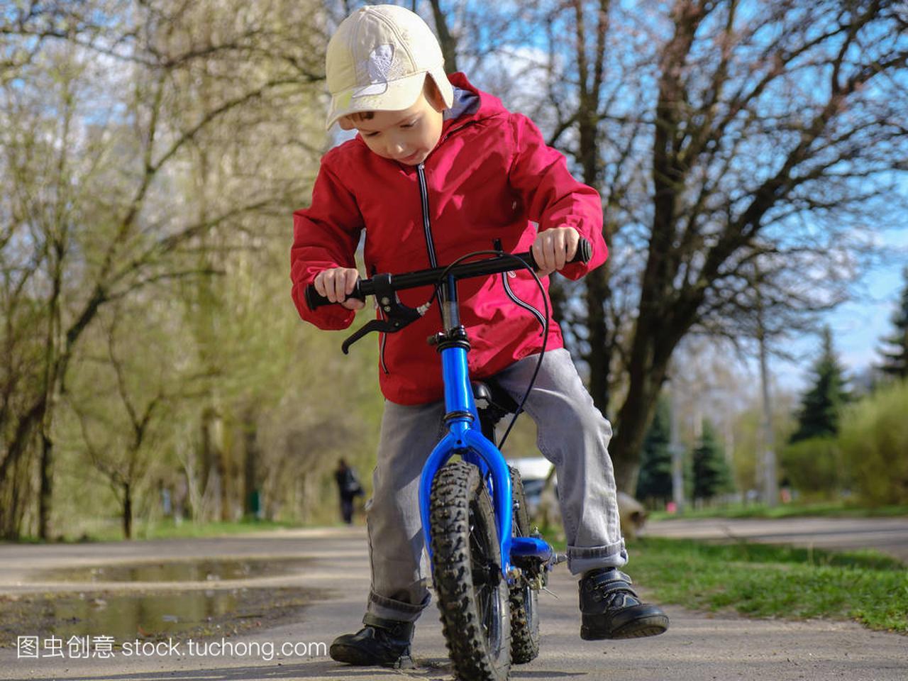 小男孩骑着他的第一辆自行车在城市公园。快乐