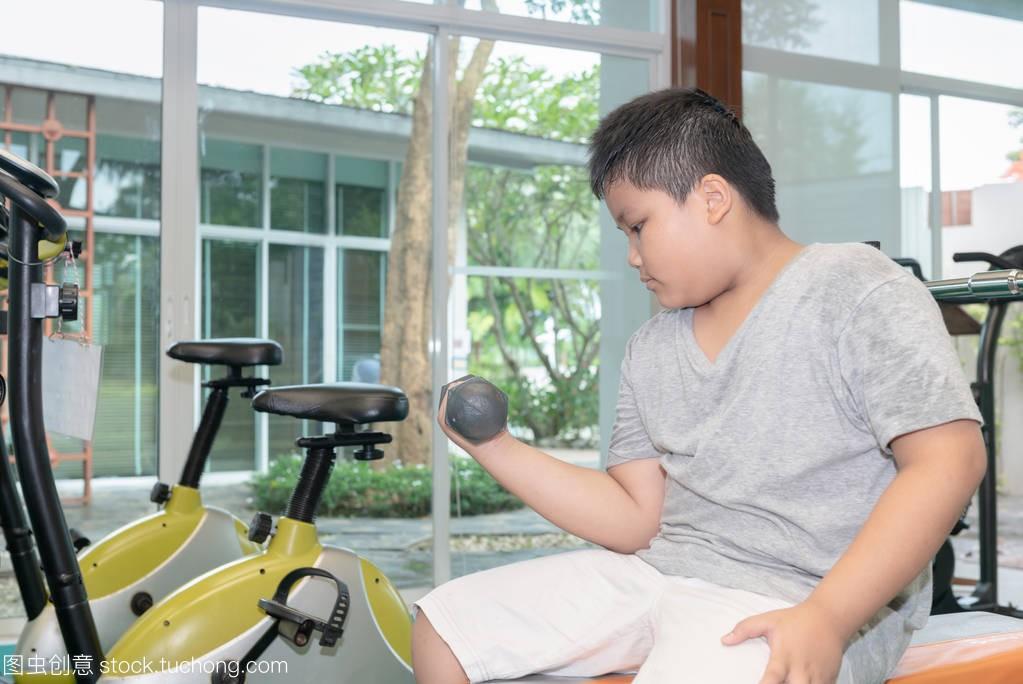 肥胖男孩在健身室举哑铃, 锻炼减肥概念