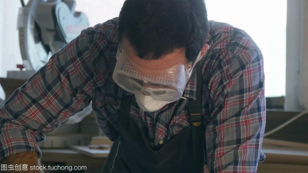 木工用工业工具在戴安全眼镜的木工厂工作