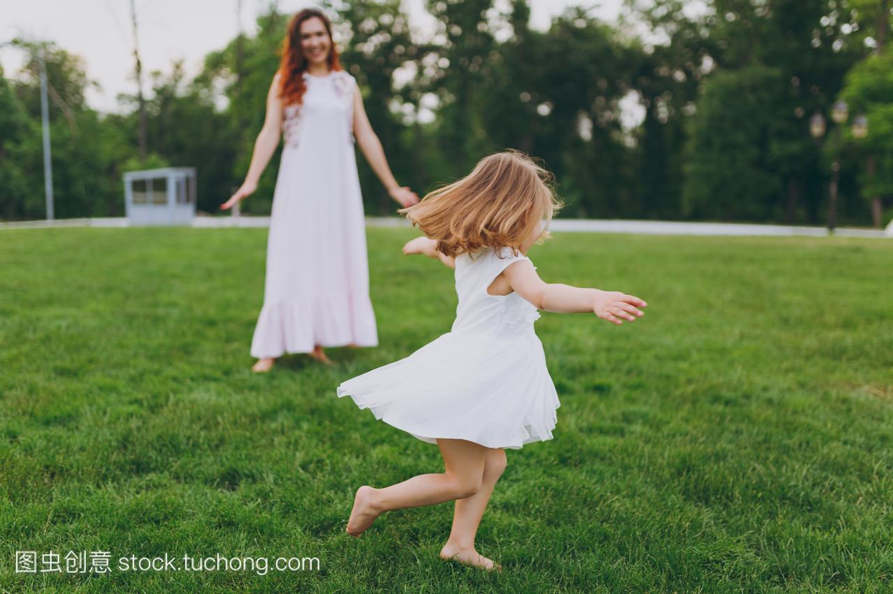 漂亮的小可爱的孩子, 穿着浅色衣服盘旋, 并在公园的草地草坪上的乐趣。妈妈小女儿母亲节, 爱家庭, 亲子, 童年概念