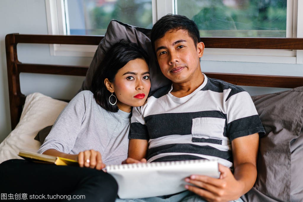 ractive Malay Asian couple sitting around lazily