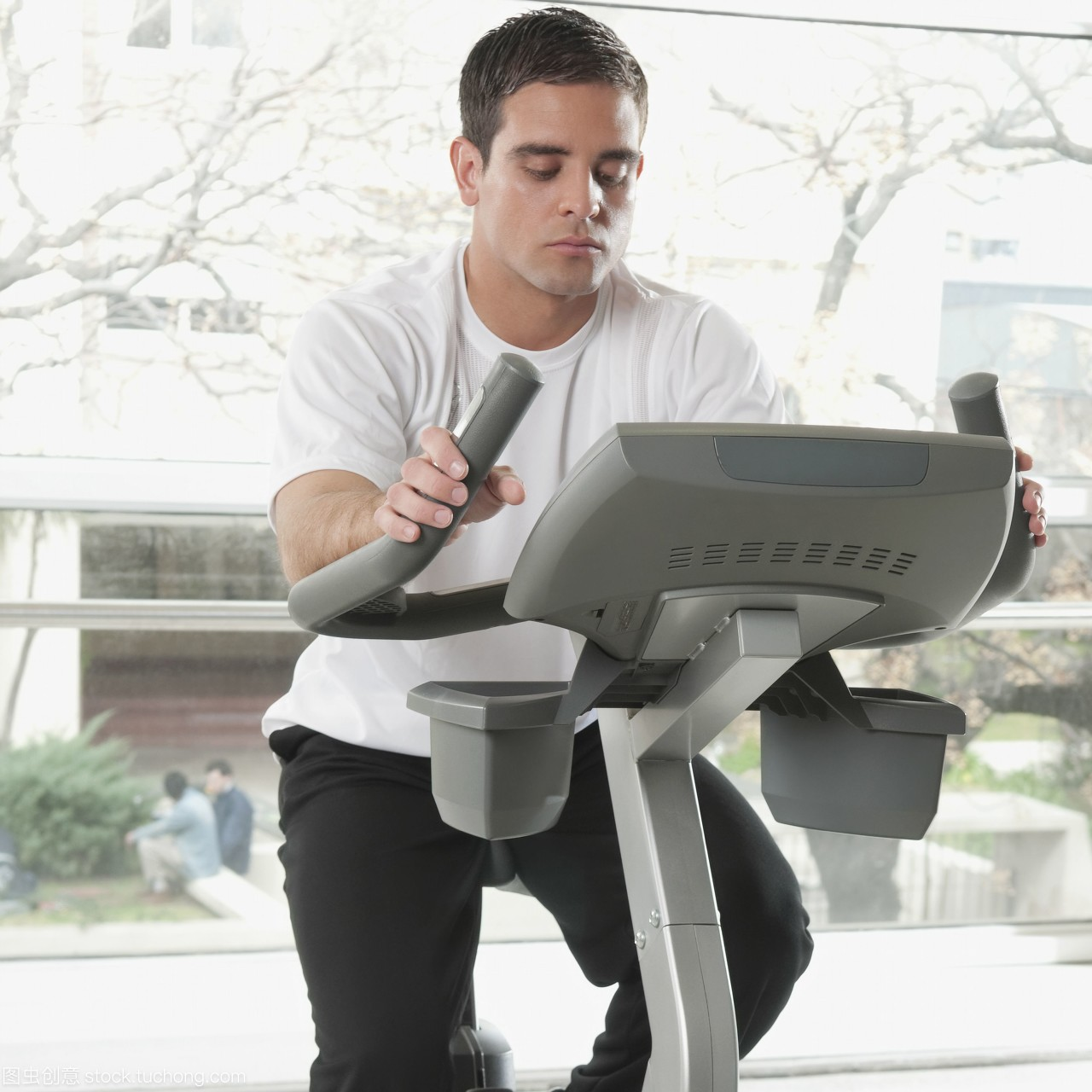 在健身房里锻炼自行车的人