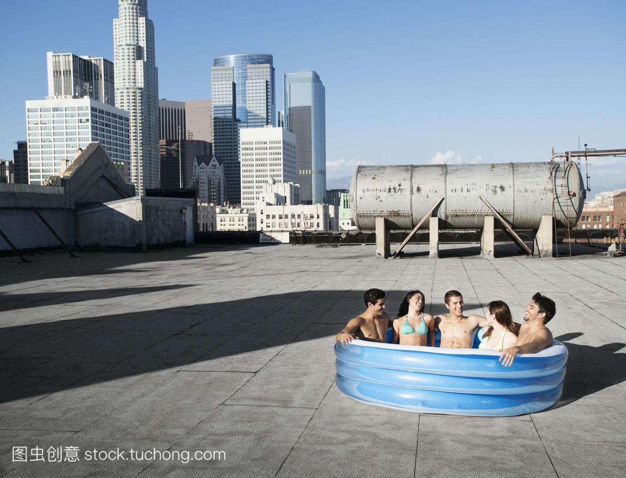 一群朋友,男男女女坐在城市屋顶的一个小充气