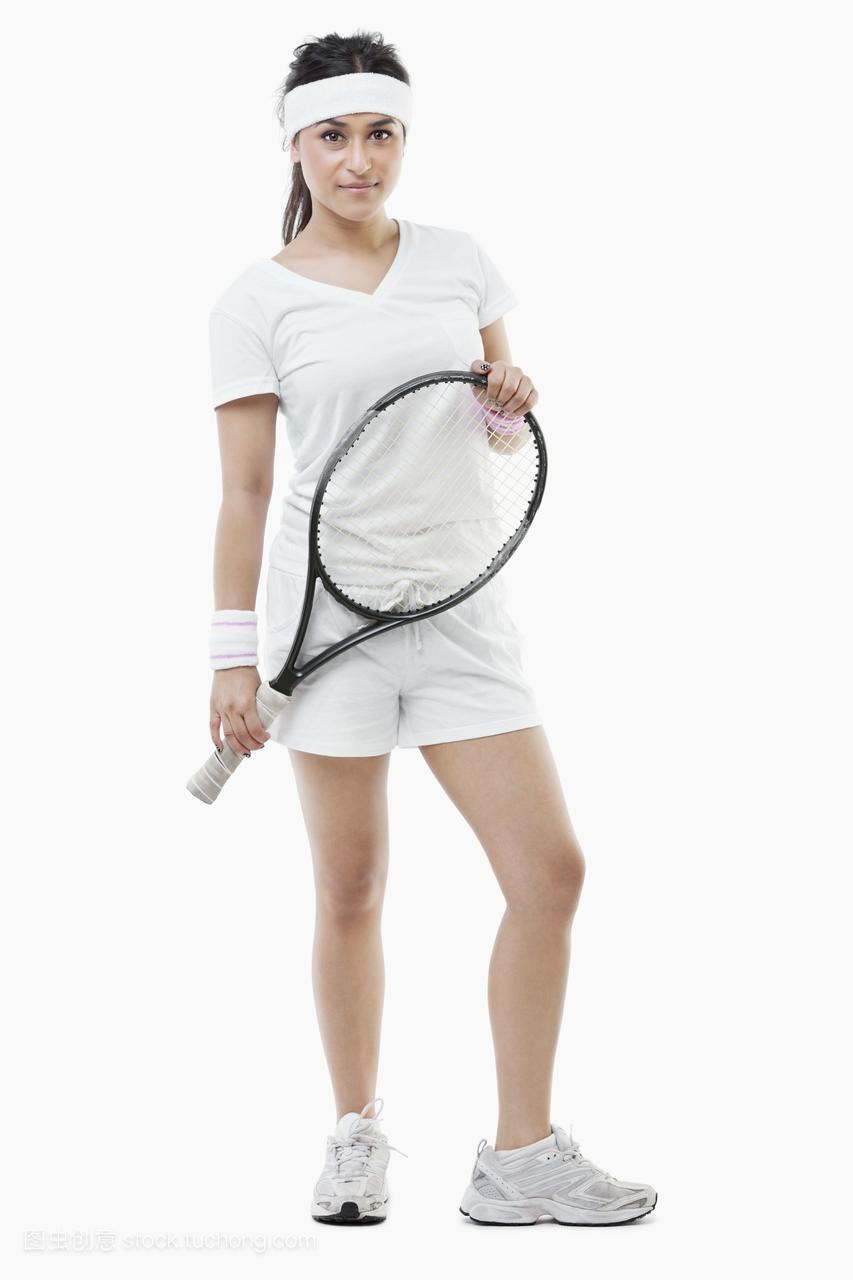 一个自信的年轻女网球运动员站在白色背景上的