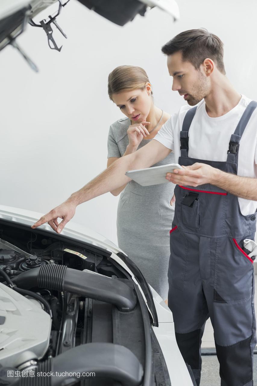 年轻的维修工人在车间里向忧心忡忡的顾客解释