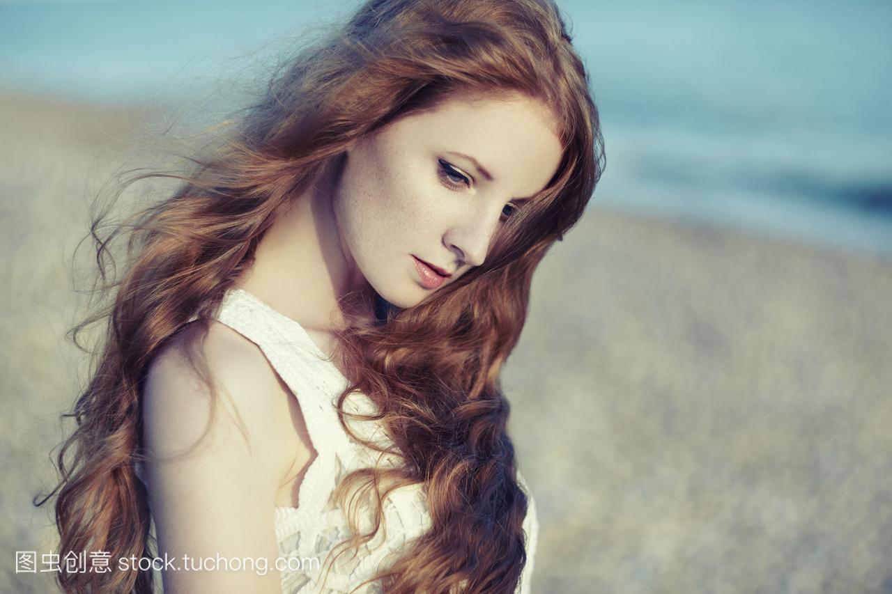 红头发的美女在大海。Fashiob照片