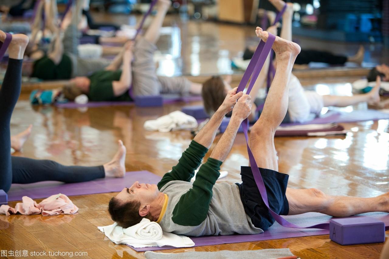 一个人使用一个瑜伽带延伸至早上拉伸瑜伽课。