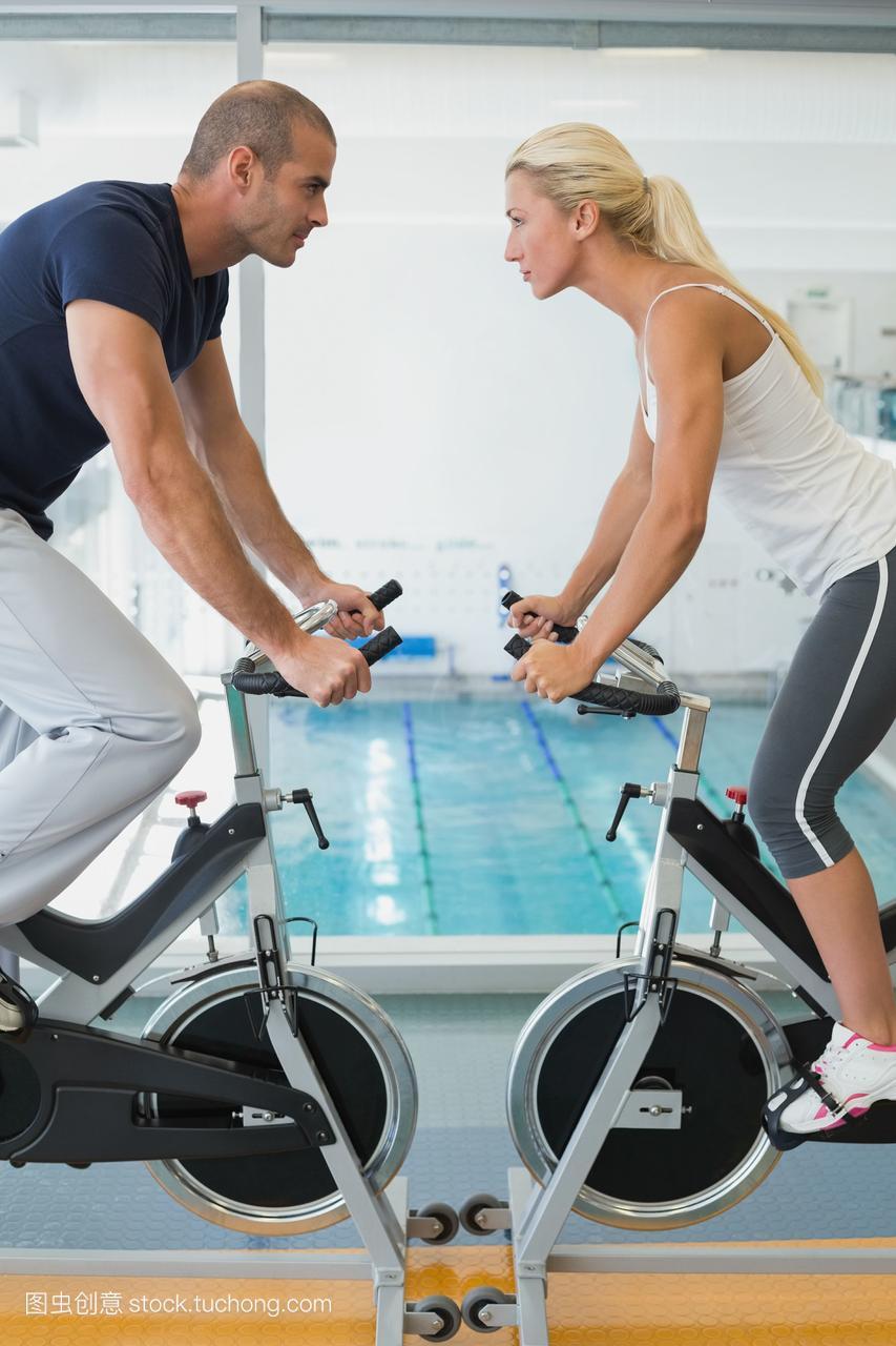 在健身房里锻炼自行车的情侣们的侧视