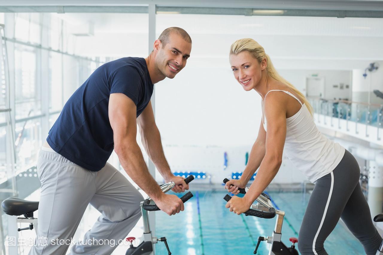 在健身房里锻炼自行车的情侣们的侧面像
