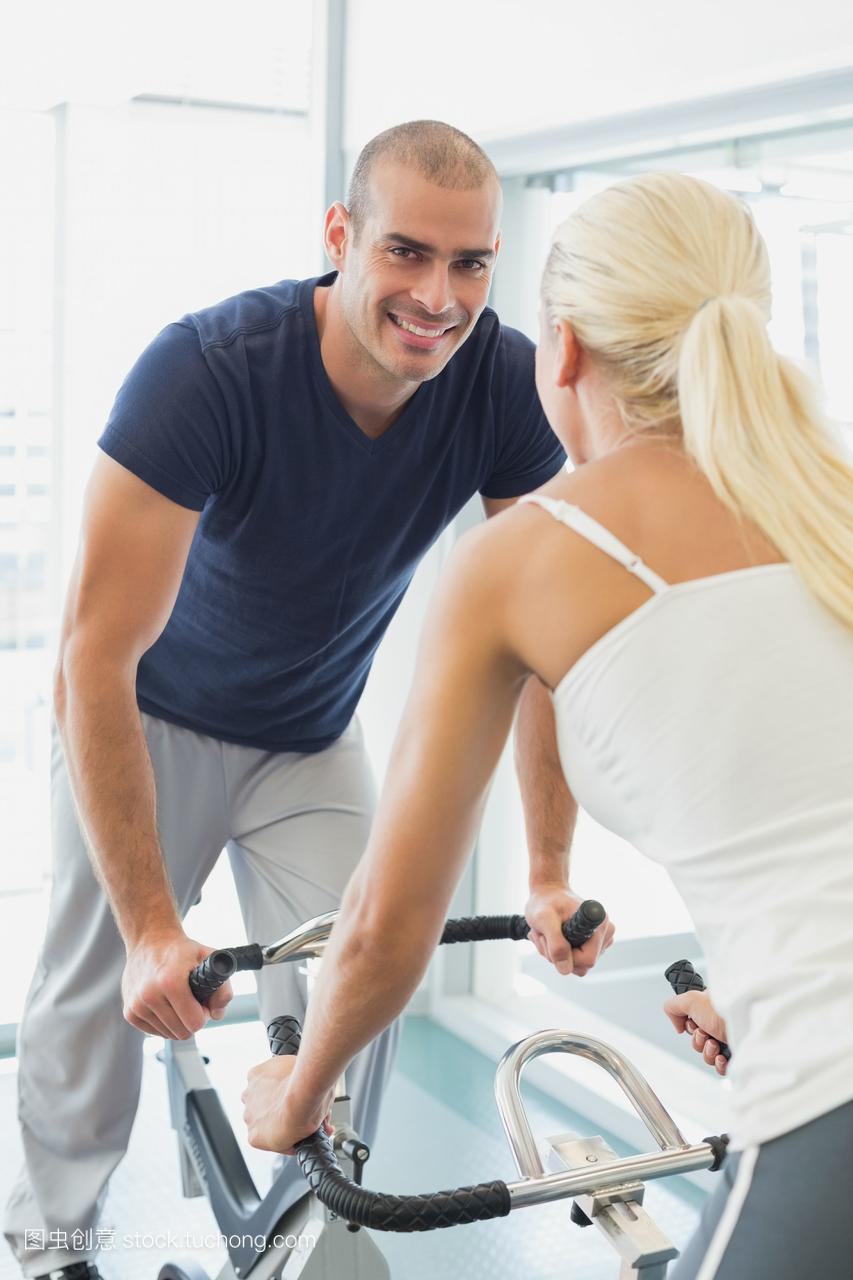在健身房里锻炼自行车的情侣们的照片