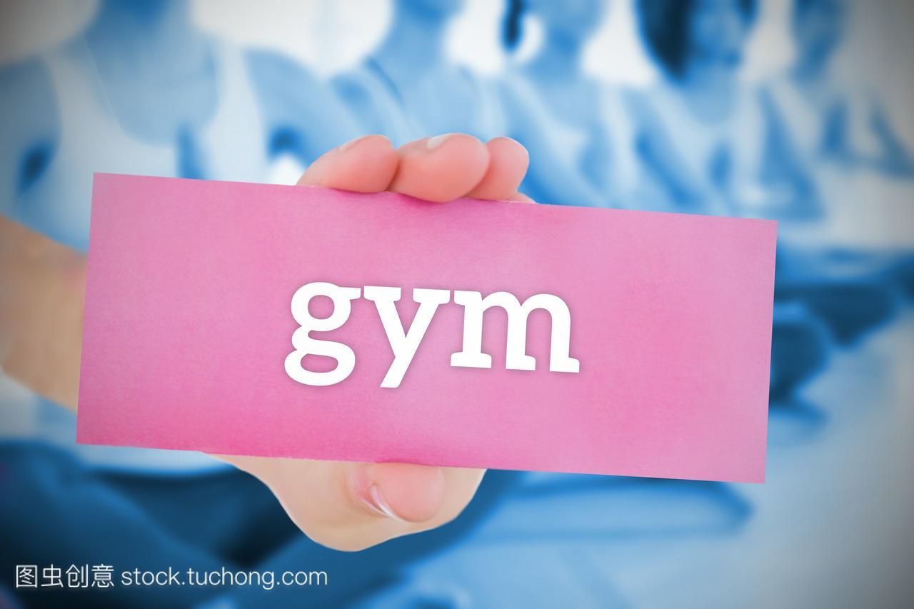 拿着粉色卡片的女人在健身房反对瑜伽课