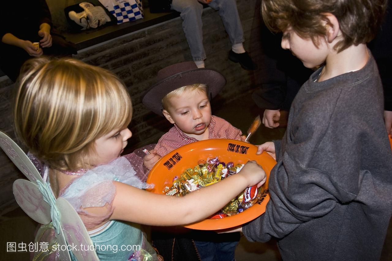 美国纽约州孩子们在万圣节服装检查碗糖果;纽约